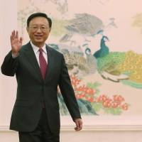 Changing times: Chinese Foreign Minister Yang Jiechi waves to reporters during a news conference at the Great Hall of the People in Beijing on March 9. Inset: Wang Yi. | AP