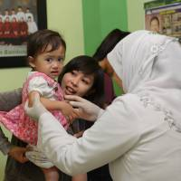 Growing pains: An Indonesian mother brings her toddler for circumcision in Bandung, West Japan Province. | AFP-JIJI
