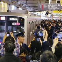 Mind the gap: Train fans gather to take photos of the final train to leave the old Tokyu Toyoko Line platform at Shibuya Station on the evening of March 15. | KYODO