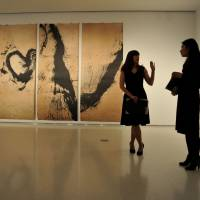 The new old: Christie's employees exchange views in front of 'The Four Seasons' (left) by Qin Feng, an ink, tea and coffee painting, and 'Scholar's Rock' by Liu Dan, a Chinese ink painting, at a gallery in New York on Wednesday. | AFP-JIJI