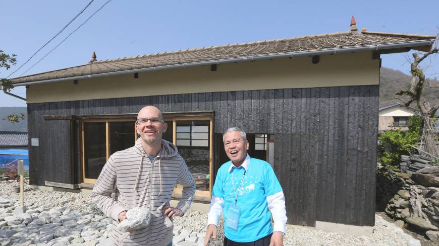 James Jack (left) talks with a volunteer in front of his 'SUNSET HOUSE: Language as the house of Being' at Shodoshima.