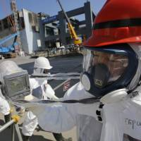 High radiation: A monitor reads 114 microsieverts per hour as members of the media and Tokyo Electric Power Co. employees, wearing protective suits, visit the No. 4 reactor building (background center) and the construction of a storage unit for melted fuel rods (background right) at Tepco's Fukushima No. 1 nuclear power plant on March 6. | BLOOMBERG