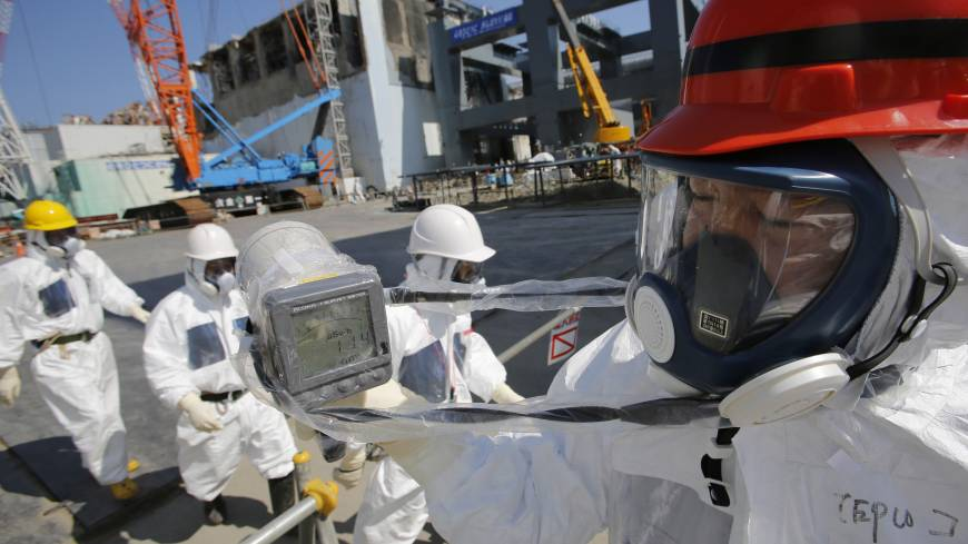 High radiation: A monitor reads 114 microsieverts per hour as members of the media and Tokyo Electric Power Co. employees, wearing protective suits, visit the No. 4 reactor building (background center) and the construction of a storage unit for melted fuel rods (background right) at Tepco's Fukushima No. 1 nuclear power plant on March 6.