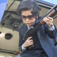 Playing with firepower: Eight-year-old actor Fuku Suzuki (playing Shigeru Ohnuma) wields a sawed-off shotgun in 'Kodomo Keisatsu' ('Kiddy Cops'), a parody of popular 1970s Japanese cop shows. | © 2013 EIGA