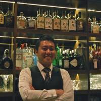 Slinging it in Singapore: Akihiro Eguchi, manager of Singapore bar Jigger & Pony, displays bottles including many Japanese whiskies. | MELINDA JOE