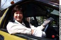 Yoko Yamaoka at the wheel of her taxi, doing the demanding job she says she enjoys because, among other things, she gets the same pay as her male colleagues.