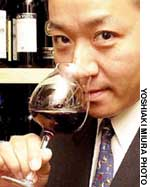 Makoto Abe, Japan's champion sommelier, checks the bouquet of a glass of red wine.