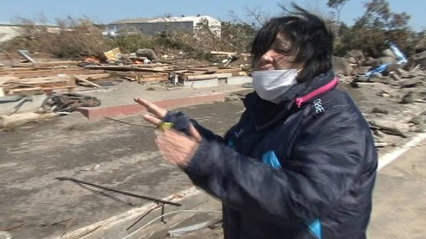 Hearing aid: Nobuko Kikuchi, a deaf resident in the city of Iwanuma, Miyagi Prefecture, shows where her house used to be before it was uprooted and washed away by the monster tsunami on March 11, 2011.