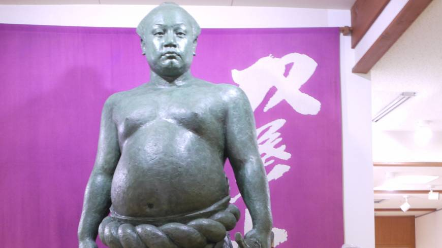 Never too chicken to fight: Usa in Oita Prefecture is famed for its museum celebrating sumo champion Futabayama Sadaji (pictured in statue form with museum director Fumitoshi Shingai).