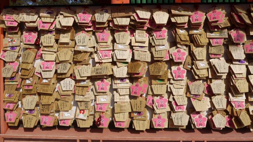 Best of luck: Usa Shrine, reached by long entrance paths that look especially pretty in a sudden snowstorm, is a 'power spot' destination for those wishing for favorable fortune.  FAR RIGHT: VISITORS TO THE SHRINE WRITE THEIR WISHES ON WOODEN  EMA