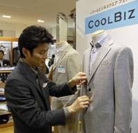 Not so cool: A shop attendant adjusts a suit at a Cool Biz clothing display in a Mitsukoshi Department Store in Tokyo in July 2005. | BLOOMBERG PHOTO