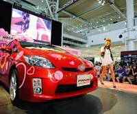 Strikes a chord: A model struts past Toyota Motor Corp.'s DecoPrius, adorned with rhinestones, crystals and stickers, during a promotional event July 20 at the automaker's showroom in Odaiba, Tokyo. | BLOOMBERG PHOTO