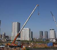 If you build it: Construction takes place in front of residential complexes in the Toyosu district of Koto Ward, Tokyo, in June. | BLOOMBERG PHOTO