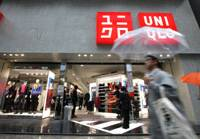 Packing them in: Pedestrians walk past Fast Retailing Co.'s Uniqlo store in Tokyo's Ginza district on Oct. 7. | BLOOMBERG PHOTO