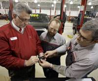 One at a time: Service manager Mitch Scott (left) and service technicians Dean Baker (center) and Dennis Mclntyre repair a gas pedal assembly at Andy Mohr Toyota in Avon, Ind., on Wednesday. | AP PHOTO