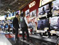 The big picture: A shopper gets a sales pitch in front of flat-panel TVs at an electronics store in Tokyo on Feb. 3. Gross domestic product grew at an annualized pace of 4.6 percent in the October-December period on pickups in consumer spending and corporate investment. | AP PHOTO