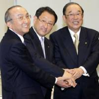 Hands-on experience: Akio Toyoda (center), then executive vice president of Toyota Motor Corp., joins hands with then President Katsuaki Watanabe (left) and Chairman Fujio Cho at a January 2009 news conference in Tokyo to announce Toyoda's appointment to the top spot. | AP PHOTO