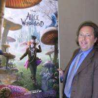 Coming attractions: IMAX Corp. Chief Executive Richard Gelfond poses next to a poster of Tim Burton's 'Alice in Wonderland' during an interview in Tokyo on Monday. | AP PHOTO