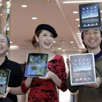 Got a new pad: Kazuaki Miura (right), the first to obtain Apple's iPad at a Softbank Corp. store in Tokyo's Harajuku district, beams Friday in a congratulatory moment with Softbank Chief Executive Masayoshi Son and model Rina Fujii. | AP PHOTO