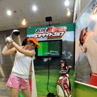 Fine form: A model tries out Epoch Co.'s virtual golf game, Ryo Ishikawa Excite Golf, at Tokyo Big Sight on Thursday. | YOSHIAKI MIURA PHOTO