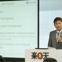 Powerful points: Rakuten Inc. Chairman and CEO Hiroshi Mikitani gives a presentation in English during a news conference Thursday to announce the firm's financial results at its head office in Shinagawa Ward, Tokyo. | KYODO PHOTO