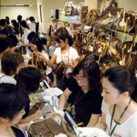 The money or the bag?: Women examine goods at a special discount sales event Wednesday at Hanshin department store in Kita Ward, Osaka. | KYODO PHOTO