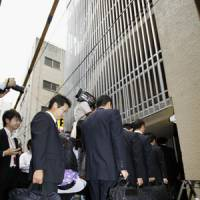 Taking over: Officials from Deposit Insurance Corporation of Japan, which will manage Incubator Bank's operations and assets during its bankruptcy proceedings, enter the bank's head office in Chiyoda Ward, Tokyo, on Friday. | KYODO PHOTO