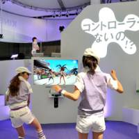 Two women play a beach volleyball video game on Microsoft's Xbox 360 console with the new Kinect camera-sensor system at the Tokyo Game Show at Makuhari Messe hall in Chiba on Thursday. | YOSHIAKI MIURA PHOTO