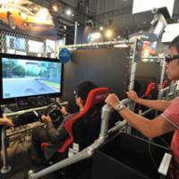 Getting in on the action: Visitors to the four-day Tokyo Game Show try playing a 3-D driving game for the Sony PlayStation 3 on Thursday at the Makuhari Messe hall in Chiba.