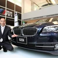 Booming business: Jun Kubota, sales manager for BMW Aoyama Square, poses next to a 523i at the company's showroom in Tokyo on May 30. | BLOOMBERG PHOTO