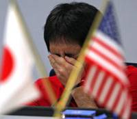 High-stakes job: A currency broker covers his face with his hand during a trading session in Tokyo last August. | AP/KYODO