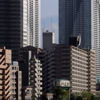Building up: Residential buildings are seen in Tokyo. Mitsui Fudosan Co. plans to triple the size of its private real-estate investment trust in three years. | BLOOMBERG