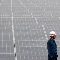 Bright hopes: A worker checks panels at the Ogishima solar power plant in Kawasaki, run by local authorities and Tokyo Electric Power Co., in December. | BLOOMBERG