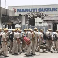Labor unrest: Indian police officers enter the vandalized Maruti Suzuki factory in Manesar, near New Delhi, on July 21. | AP