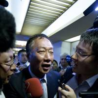 In Sharp focus:  Terry Gou, chairman of Hon Hai Precision Industry Co., is surrounded by reporters Monday as he leaves a  Tokyo news conference. | BLOOMBERG