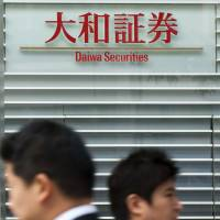 Cost-cutting blur: People walk past the building housing Daiwa Securities Group Inc.'s headquarters in Tokyo last year. | BLOOMBERG