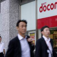 Busy signal: Pedestrians walk past an NTT DoCoMo store in Tokyo on Oct. 26. | BLOOMBERG
