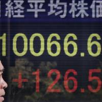 Tailwind: A man passes a quotation board of a Tokyo brokerage Tuesday, when the stock index jumped. Japanese government bonds are meanwhile headed for their longest run of annual gains. | AP