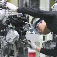 In working order: A worker inspects an engine for Toyota Motor Corp.'s Aqua hybrid compact on the production line of Toyota Motor East Japan Inc.'s Taiwa plant in Miyagi Prefecture in mid-December. | BLOOMBERG