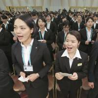 'Iiiiiiiiiiii kibun!': New employees at Seven & I Holdings Co. participate in a sing-along at the retailer's welcoming ceremony Thursday before kicking off the start of the new fiscal year in April. | KYODO