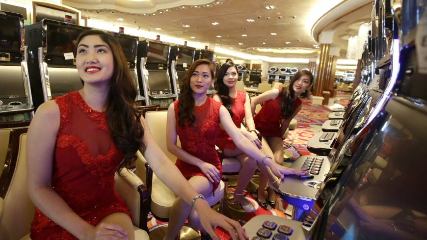 Roll the dice: Casino models pose at the slot machines during a media tour of the Philippines' new Solaire Casino on Thursday in suburban Pasay. Michael French, chief operating officer of Solaire Resort and Casino, said studies not commissioned by his company project Filipino gaming revenue could rise from $1.9 billion to $6 billion, equivalent to Singapore's revenue, in about five years.