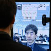 Counting the beats: A Fujitsu Ltd. engineer demonstrates a system for monitoring one's pulse that uses facial imaging technology accessed through a Web camera on a computer or smartphone, at the company's headquarters in Tokyo on Monday. | AFP-JIJI