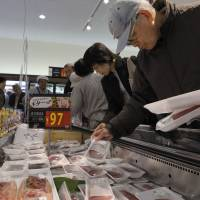 Catch of the day: Customers select fish and other food items at a Seiyu GK superstore in Tokyo last November. | BLOOMBERG