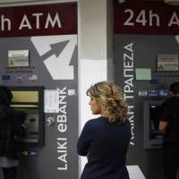 Use it or lose it: A woman waits as two people use ATMs in Nicosia on Friday. | AP