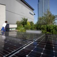 Bright future?: Solar panels sit on the rooftop of Panasonic Corp.'s eco ideas House, a model home touted for its virtually zero carbon-dioxide emissions, at Panasonic Center Tokyo in July 2011. | BLOOMBERG