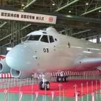 In the hunt: Kawasaki Heavy Industries Ltd.'s P-1 next-generation antisubmarine patrol aircraft is unveiled at its plant in Gifu Prefecture on Tuesday. The new aircraft will be used by the Maritime Self-Defense Force. | KYODO