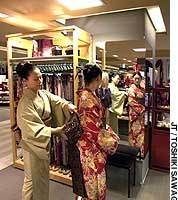 A sales clerk helps Chika Ito try on a kimono at the Tobu department store in Ikebukuro, Tokyo.