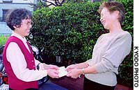 An unidentified resident (left) of Takarazuka, Hyogo Prefecture, receives local community currency from Yosuko Takamatsu, head of Mefu no Ouchi.