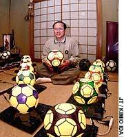 Kazuhide Yoshikawa holds one of his stained-glass soccer ball lamp shades, which are patented in 21 countries.