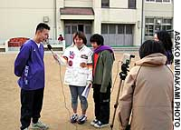 Children at Shinyo Elementary School in Kobe's Nagata Ward interview their teacher as part of their video film on local issues.